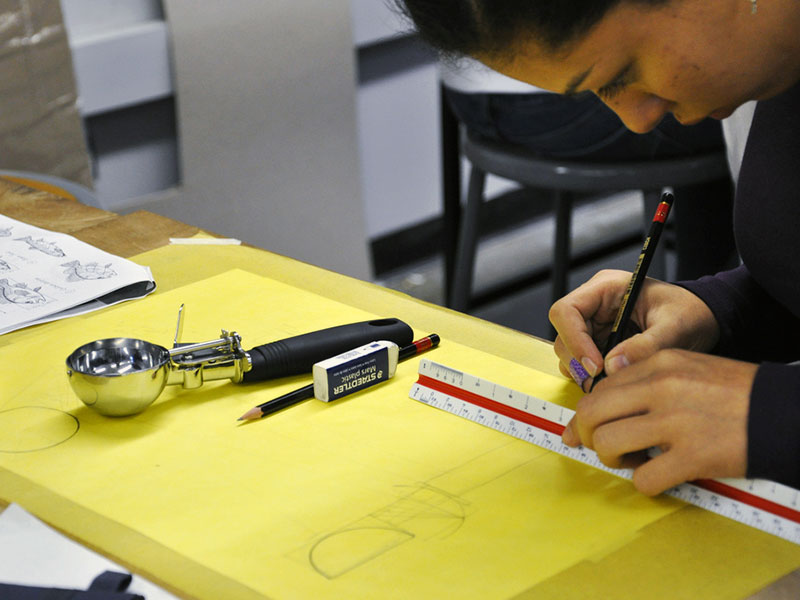 Woman drafts a sketch of an ice cream scoop mechanism for a Design Bloc course.