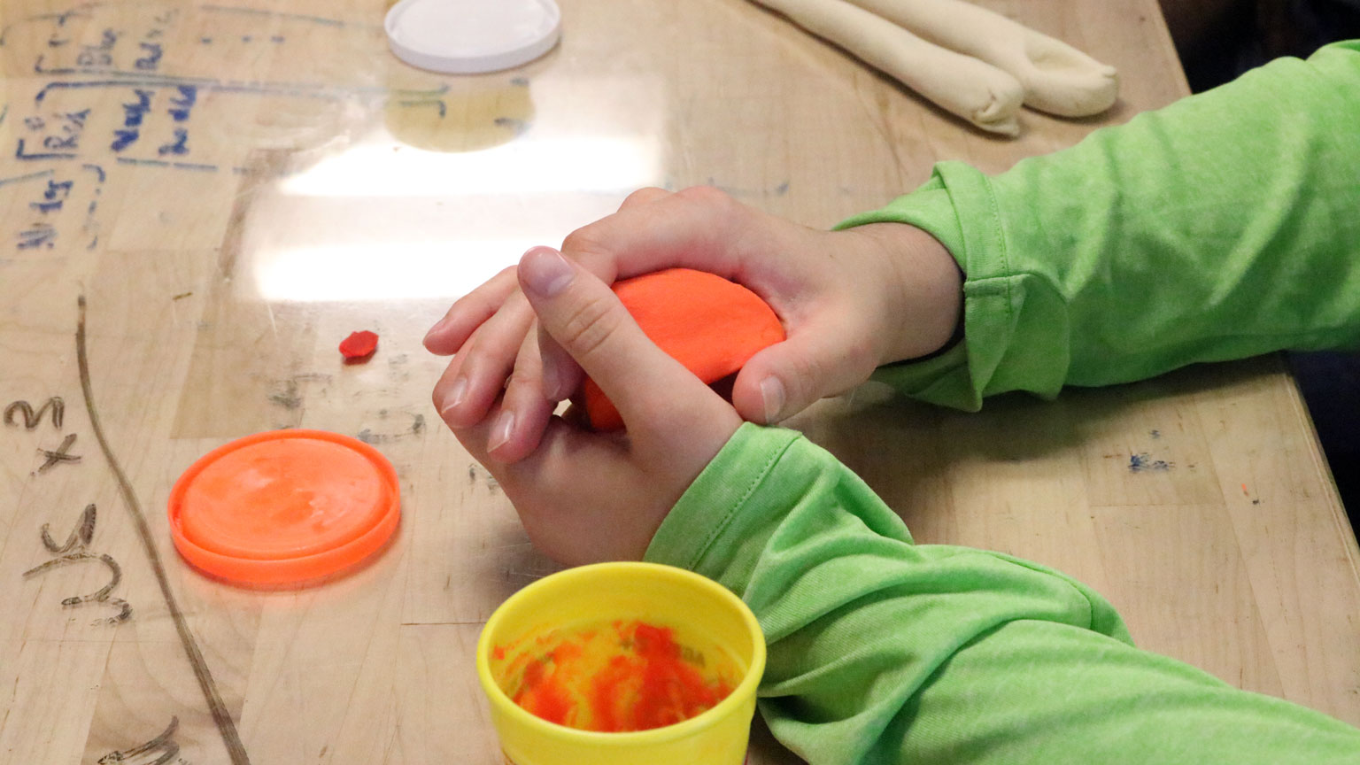Hands mold dough into prototype utensil during a Design Bloc workshop on empathy for the user.