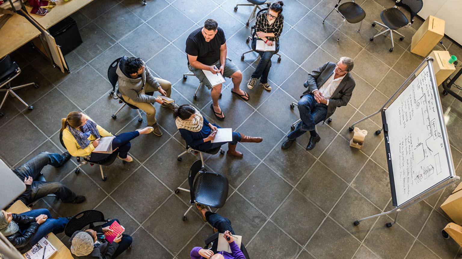 Students gather in a circle around a professor and jot down notes during the Design Methods course.