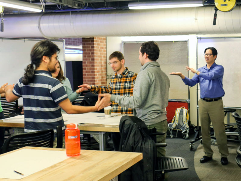Coworkers take part in an improv-inspired warmup activity before learning how to brainstorm ideas in a Design Bloc workshop.