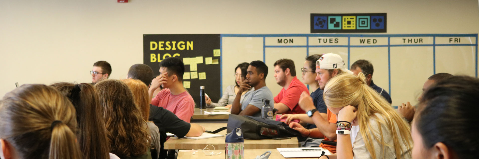 An audience of students, viewed from the side, listens intently to a Design Bloc professor at the front of the class.