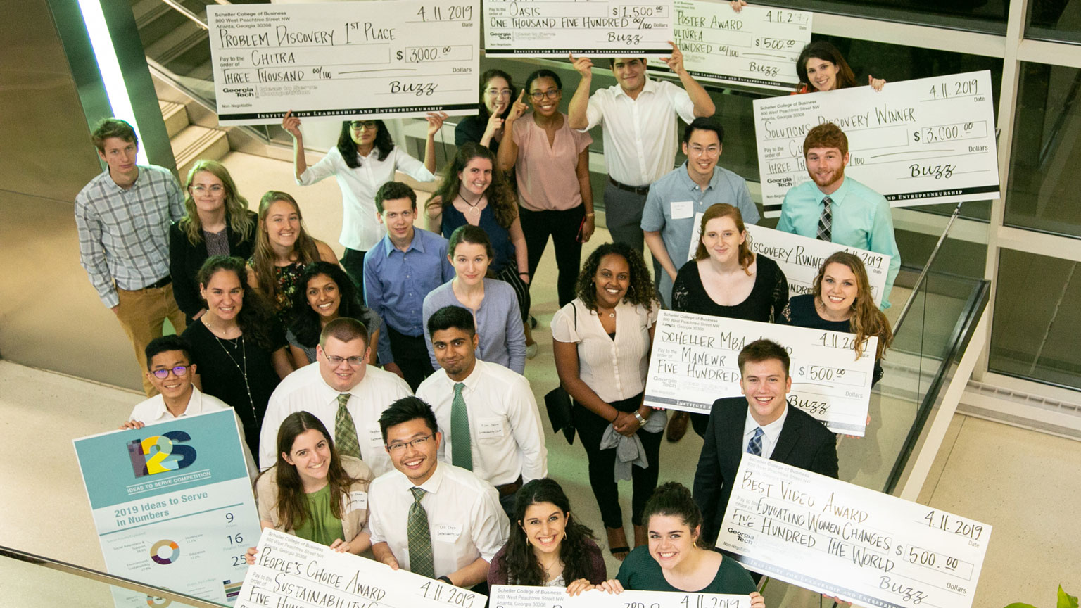 Students from Social Impact: In Depth Exploration and Design show the grants they received for their projects during Georgia Tech's Ideas to Serve competition.