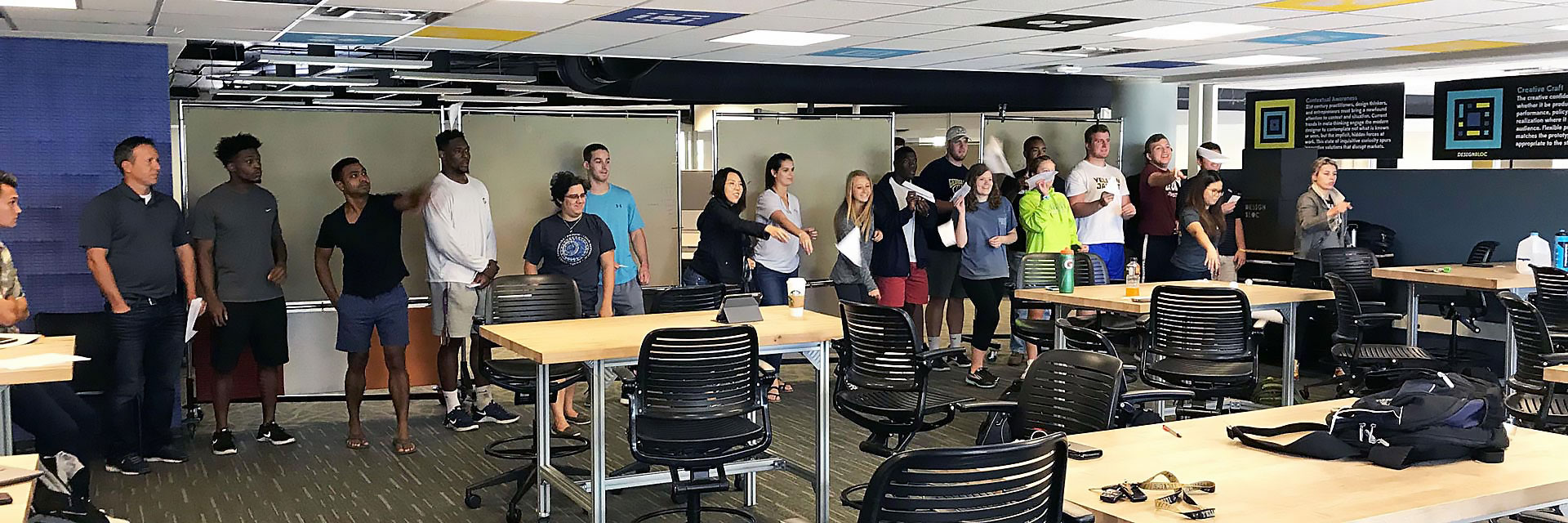 Participants in a Rapid Iteration workshop sail their paper airplanes across the classroom during one iteration of testing.