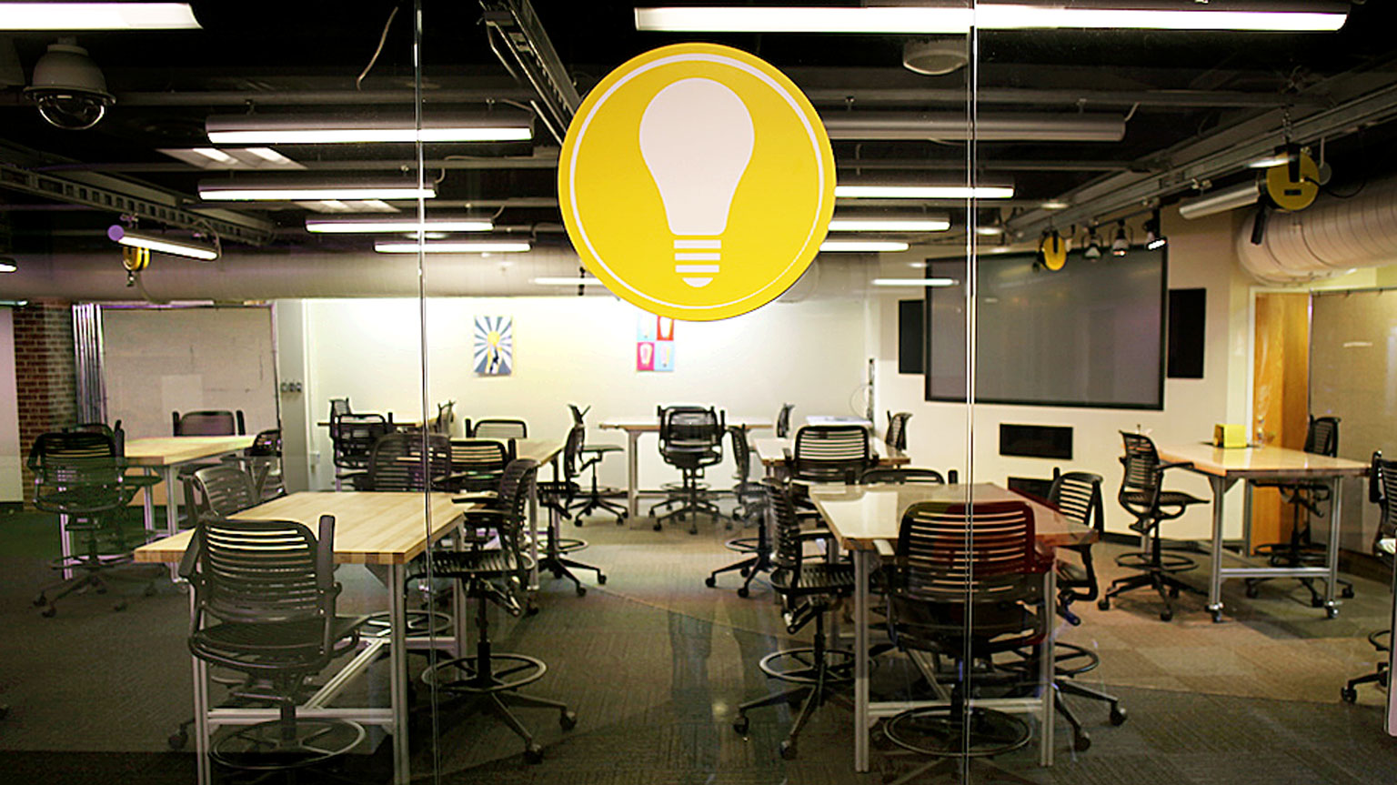 View into a classroom full of rolling tables and chairs, a presentation screen in the background, and a large lightbulb symbol hanging from the glass wall in center-view..
